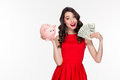 Attractive happy young curly woman holding piggy bank and money