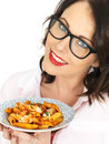 Attractive Happy Young Hispanic Woman Holding a Plate of Tomato and Basil Penne Pasta Royalty Free Stock Photo
