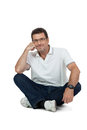 Attractive healthy adult man sitting on floor with jeans isolated glasses and t shirt casual lifestyle Royalty Free Stock Photos