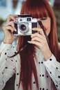 Attractive hipster woman using old fashioned camera in the garden Stock Photos