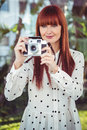 Attractive hipster woman using old fashioned camera in the garden Stock Images