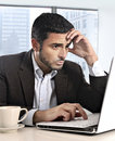 Attractive Hispanic businessman working with computer looking stressed and worried facing work issue