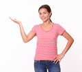 Attractive hispanic girl holding up her right hand portrait of on red t shirt and blue jeans while standing and smiling at you on Stock Image