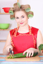 Attractive housewife cutting cucumber in the kitchen Stock Image