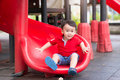 Attractive little boy on a slide in a playground Royalty Free Stock Photo