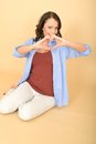 Attractive lustful romantic happy young woman making heart shape with hands a dslr royalty free image a sitting on floor looking Royalty Free Stock Photos