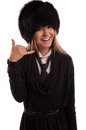 Attractive making a call me gesture wearing fur hat and black tie Stock Photos