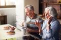 Attractive male and female pensioners having breakfast in the kitchen Royalty Free Stock Photo