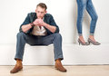Attractive male model sitting with a pair of female legs on the side portrait an Stock Photo
