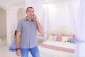 Attractive male talking on smartphone in light bedroom on backgr