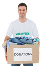 Attractive man holding donation box with clothes on white background Royalty Free Stock Photo