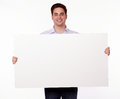 Attractive man holding up a placard portrait of an young blank while standing and smiling at you on isolated background copyspace Royalty Free Stock Image