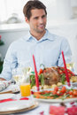 Attractive man sitting at table for christmas dinner with a roast chicken Royalty Free Stock Photos