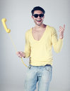 Attractive man smiling and playing with a phone Stock Photography