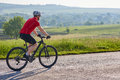 Attractive man in white helmet riding a bike on country road. Royalty Free Stock Photo
