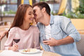 Attractive man and woman are relaxing in cafe beautiful young loving couple is dating restaurant they sitting near each other the Stock Photography