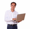 Attractive mature man using his laptop portrait of an while standing and looking at you on isolated studio Stock Images