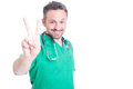 Attractive medic showing peace sign or number two Royalty Free Stock Photo