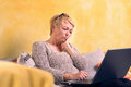 Attractive middle aged woman using a laptop at home as she relaxes on comfortable sofa sitting looking pensively at the screen Royalty Free Stock Image