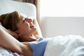 Attractive Middle Aged Woman Waking Up In Bed Royalty Free Stock Photo