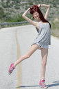 Attractive model standing in the middle of a mountain road Royalty Free Stock Photo