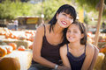 Attractive mother and daughter portrait at the pumpkin patch baby in a rustic ranch setting Royalty Free Stock Photos