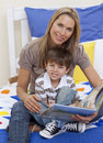 Attractive mother reading a book with her son Royalty Free Stock Images