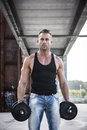Attractive muscular hunk man lifting weights outdoor handsome showing healthy body while looking at the camera Stock Photography