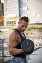 Attractive muscular hunk man lifting weights outdoor handsome showing healthy body while looking at muscle Royalty Free Stock Images