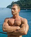 Attractive muscular young man outside in front of the sea arms crossed handsome bodybuilder outdoors with and behind Royalty Free Stock Photography