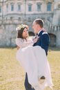 Attractive newlywed couple at green lawn near beautiful ruined baroque palace. Loving groom holding charming bride on Royalty Free Stock Photo