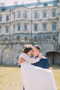 Attractive newlywed pair at green lawn near beautiful ruined baroque palace. Loving groom holding charming bride on his Royalty Free Stock Photo