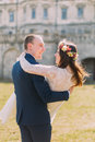 Attractive newlywed pair at green sunny lawn near beautiful ruined baroque palace. Loving groom holding charming bride Royalty Free Stock Photo