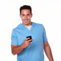 Attractive nurse man texting with his cellphone portrait of an on blue uniform while standing and smiling at you on isolated Royalty Free Stock Photos