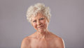 Attractive old woman looking happy studio shot of shirtless senior female against grey background Stock Images