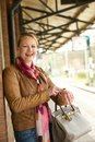 Attractive older woman smiling and pointing to her watch portrait of an at train station Royalty Free Stock Photography