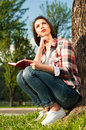 Attractive pensive female sitting outdor in the park with diary next to an old tree Stock Photos