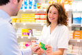 Attractive pharmacist taking healt insurance card view of an Royalty Free Stock Photography
