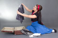 Attractive pinup girl packing retro suitcase over grey Royalty Free Stock Photo