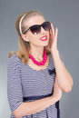 Attractive pinup girl in sunglasses over grey Royalty Free Stock Photos