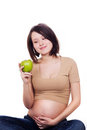 Attractive pregnant woman holding an apple Stock Photos