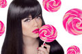 Attractive pretty girl with pink lips holding lollipop over swee Royalty Free Stock Photo