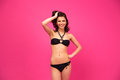 Attractive pretty woman posing in bikini black over pink background Royalty Free Stock Photo