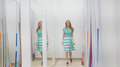 Attractive red hair girl chooses green dress near mirror in fitting room at store