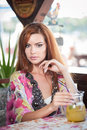 Attractive red hair young woman with bright colored blouse drinking lemonade on a terrace. Gorgeous redhead model drinking fresh d Royalty Free Stock Photo