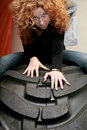Attractive redhead on tire Royalty Free Stock Photography
