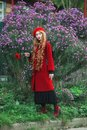 Attractive redhead woman in coat on flower background. Fashion model with long red hair with red flower in hand. Shoes and stylish Royalty Free Stock Photo