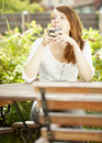 Attractive redhead woman daydreaming sitting at a rustic wooden table enjoying a relaxing cup of coffee in the garden Stock Images