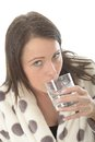 Attractive relaxed young woman feeling poorly drinking a glass of water wearing warm cosy spotty dressing gown and unwell looking Stock Image