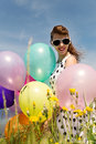 Attractive rockabilly girl with balloons in the nature sunglasses and a suicide roll a dotted dress from s and Stock Photo